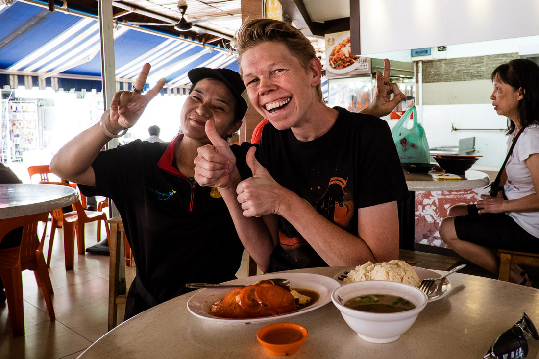 I eat chicken rice and smile every day! The woman is one of the ladies selling drinks at the hawker center. Image by Charlene Winfred.