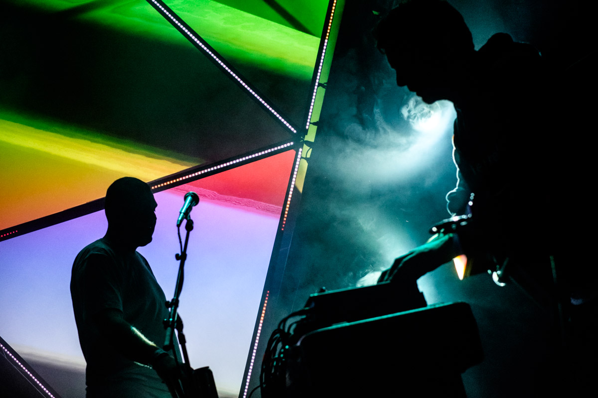 A tight composition, cutting out colours and shapes from the silhouettes and stage light.