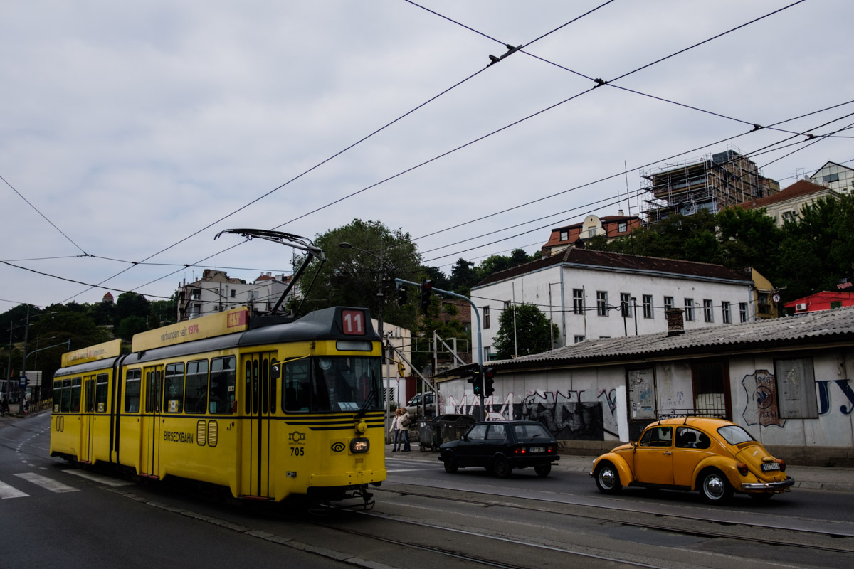 A bit of history here, a yellow tram passes a yellow VW beetle and a Yugo car!